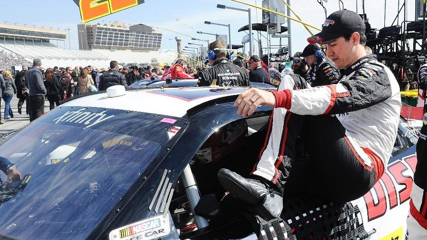 Driver Joey Lagano climbs into his car for the start of the NASCAR Xfinity series auto race Saturday, Feb. 28, 2015, in Hampton, Ga.  (AP Photo/John Amis)