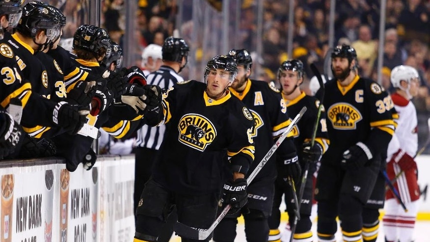 Boston Bruins' Brad Marchand is congratulated at the bench after scoring against the Arizona Coyotes during the first period of an NHL hockey game in Boston Saturday, Feb. 28, 2015. (AP Photo/Winslow Townson)