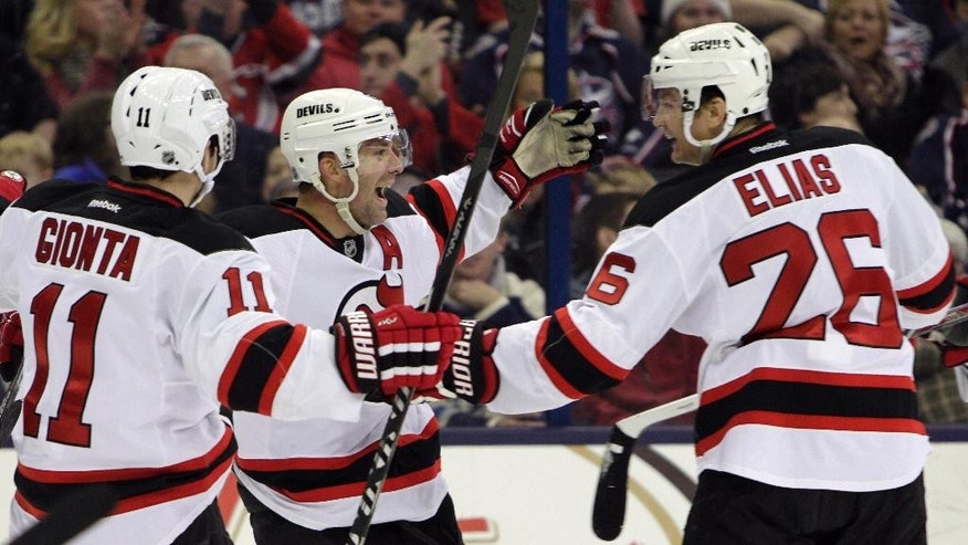 New Jersey Devils' Andy Greene, center, celebrates his goal against the Columbus Blue Jackets with teammates Stephen Gionta, left, and Patrik Elias, of the Czech Republic, during the first period of an NHL hockey game Saturday, Feb. 28, 2015, in Columbus, Ohio. (AP Photo/Jay LaPrete)