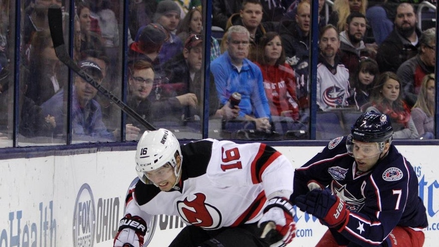 New Jersey Devils' Jacob Josefson, left, of Sweden, carries the puck behind the net as Columbus Blue Jackets' Jack Johnson defends during the first period of an NHL hockey game Saturday, Feb. 28, 2015, in Columbus, Ohio. (AP Photo/Jay LaPrete)
