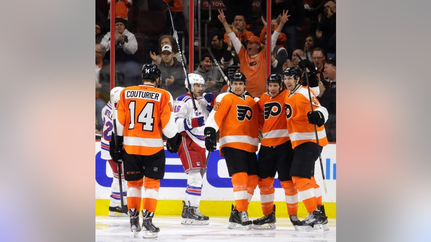 Philadelphia Flyers' Sean Couturier (14), Chris VandeVelde (76) Michael Del Zotto (15) and Braydon Coburn (5)  celebrate after Del Zotto's go-ahead goal during the third period of an NHL hockey game against the New York Rangers, Saturday, Feb. 28, 2015, in Philadelphia. Philadelphia won 4-2. (AP Photo/Matt Slocum)
