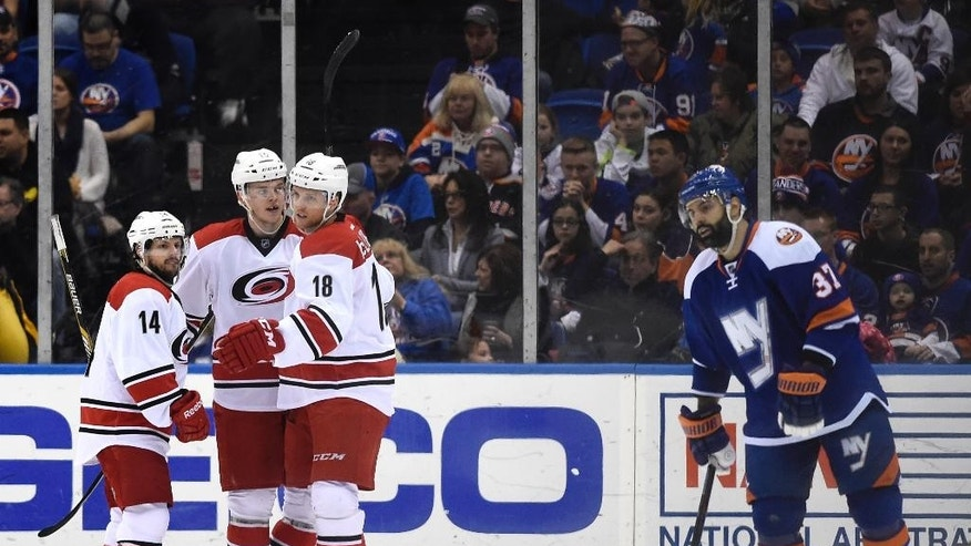 Carolina Hurricanes center Jay McClement (18) celebrates his goal left wing Nathan Gerbe (14) and right wing Andrej Nestrasil (15) as New York Islanders defenseman Brian Strait (37) reacts in the second period of an NHL hockey game Saturday, Feb. 28, 2015, in Uniondale, N.Y. (AP Photo/Kathy Kmonicek)