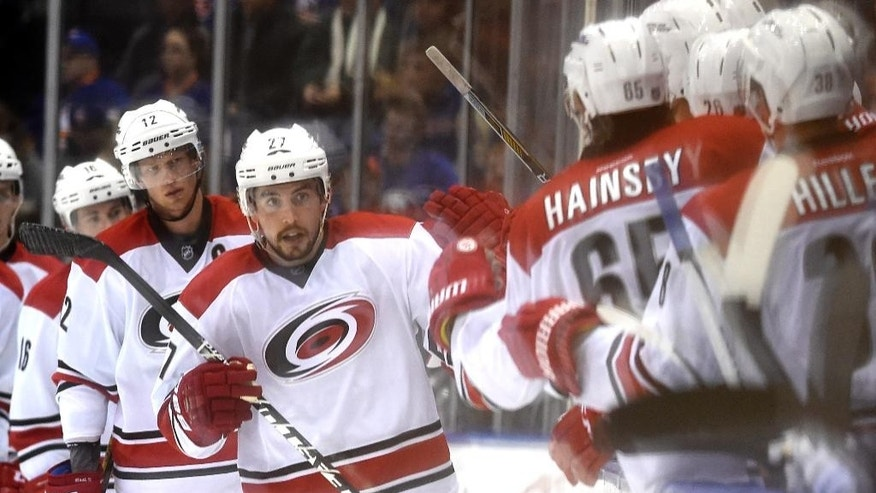 Carolina Hurricanes defenseman Justin Faulk (27) celebrates his goal with teammates in the second period of an NHL hockey game against the New York Islanders, Saturday, Feb. 28, 2015, in Uniondale, N.Y. (AP Photo/Kathy Kmonicek)