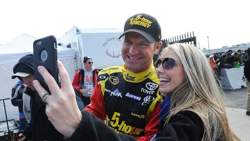 Driver Clint Bowyer poses for a photo with a fan before practicing for Sunday's NASCAR Spring Cup Series auto race, Saturday, Feb. 28, 2015, in Hampton, Ga.  (AP Photo/John Amis)