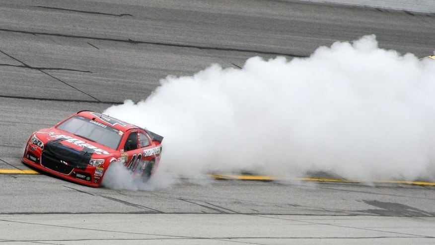 Smoke pours from Landon Cassill's (40) car during the NASCAR Sprint Cup series auto race at Atlanta Motor Speedway, Sunday, March 1, 2015, in Hampton, Ga. (AP Photo/Dale Davis)