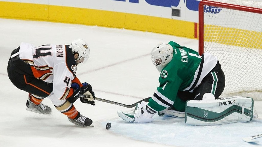 Dallas Stars goalie Jhonas Enroth (1) tries to glove the puck against Anaheim Ducks center Nate Thompson (44) in the first period of an NHL hockey game Sunday, March 1, 2015, in Dallas.  (AP Photo/Tim Sharp)