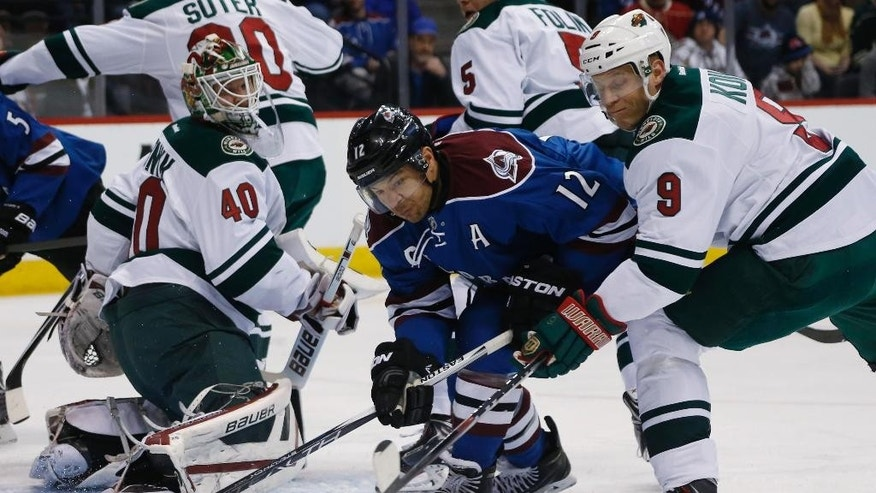 Colorado Avalanche right wing Jarome Iginla, center, fights for control of the puck as Minnesota Wild goalie Devan Dubnyk, left, and center Mikko Koivu, of Finalnd, defend in the first period of an NHL hockey game Saturday, Feb. 28, 2015, in Denver. (AP Photo/David Zalubowski)