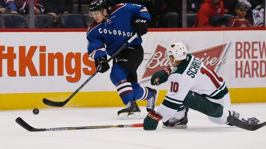 Colorado Avalanche center Nathan MacKinnon, back, uncorks a shot past the stick of Minnesota Wild center Jordan Schroeder in the first period of an NHL hockey game Saturday, Feb. 28, 2015, in Denver. (AP Photo/David Zalubowski)