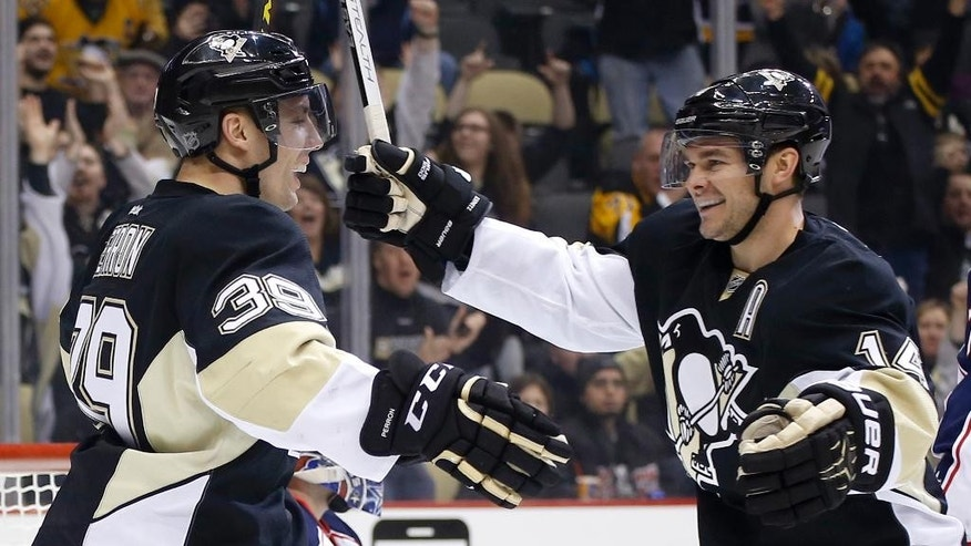 Pittsburgh Penguins' David Perron (39) is greeted by Chris Kunitz (14) after scoring against the Columbus Blue Jackets in the second period of an NHL hockey game, Sunday, March 1, 2015, in Pittsburgh. (AP Photo/Keith Srakocic)