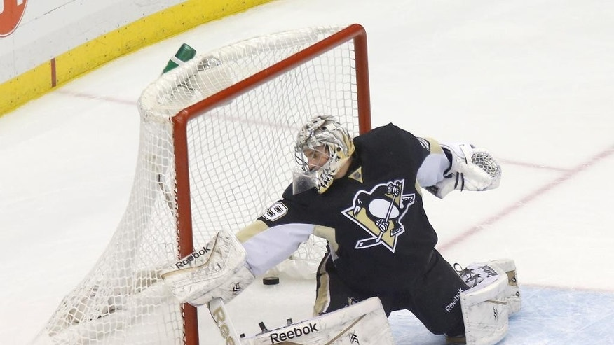 The puck gets past Pittsburgh Penguins goalie Marc-Andre Fleury (29) for a goal on a shot by Columbus Blue Jackets' James Wisniewski in the first period of an NHL hockey game, Sunday, March 1, 2015, in Pittsburgh. (AP Photo/Keith Srakocic)