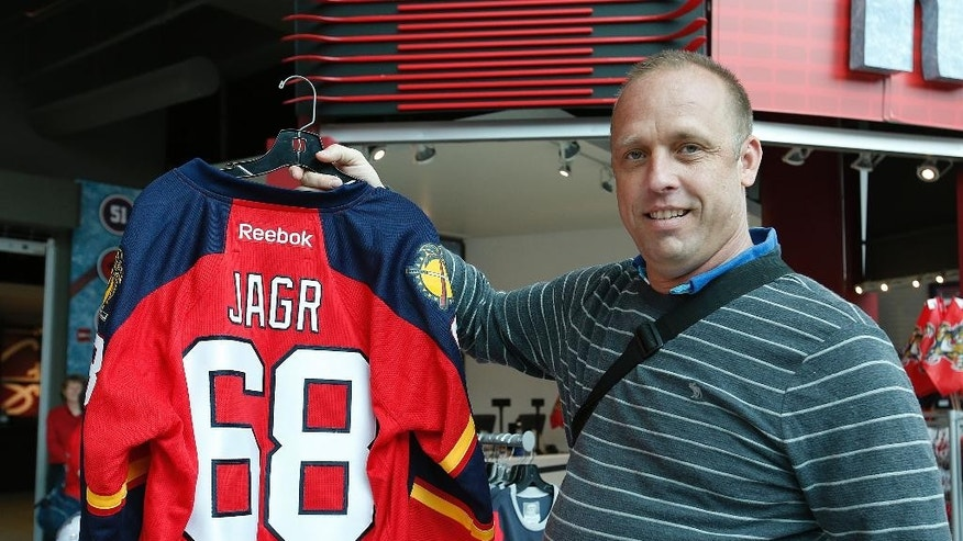 Martin Koska prepares to purchase the first Jaromir Jagr jersey in the Pantherland store prior to the NHL hockey game against the Buffalo Sabres, Saturday, Feb. 28, 2015, in Sunrise, Fla. Jagr was traded from the New Jersey Devils to the Panthers earlier on the week. (AP Photo/Joel Auerbach)
