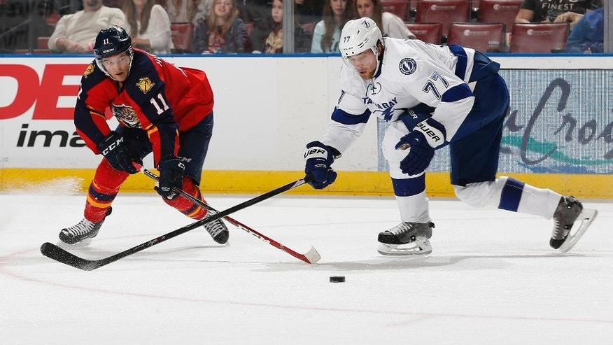 Florida Panthers forward Jonathan Huberdeau (11) and Tampa Bay Lightning's defenseman Victor Hedman (77) cross sticks as they go after a loose puck during the second period of an NHL hockey game, Sunday, March 1, 2015, in Sunrise, Fla. (AP Photo/Joel Auerbach)
