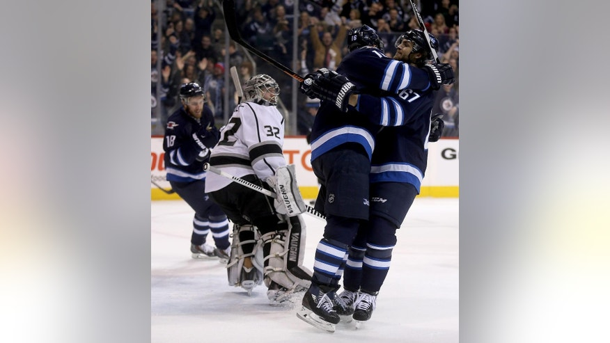 Winnipeg Jets' Andrew Ladd (16)  and Michael Frolik (67) celebrate after Ladd scored his second goal of the game against the Los Angeles Kings' goaltender Jonathan Quick (32) during second period NHL hockey action in Winnipeg, Manitoba, Sunday, March 1, 2015. (AP Photo/The Canadian Press, Trevor Hagan)