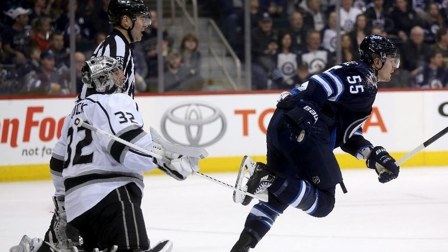 Los Angeles Kings' goaltender Jonathan Quick (32) trips Winnipeg Jets' Mark Scheifele (55) as he skates away during second period NHL hockey action in Winnipeg, Manitoba, Sunday, March 1, 2015. No penalty was called. (AP Photo/The Canadian Press, Trevor Hagan)