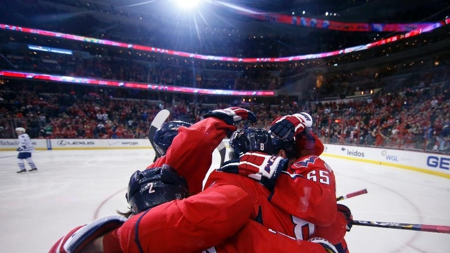 Teammates surround Washington Capitals left wing Alex Ovechkin (8), from Russia, to celebrate after his goal in the first period of an NHL hockey game against the Toronto Maple Leafs, Sunday, March 1, 2015, in Washington. (AP Photo/Alex Brandon)