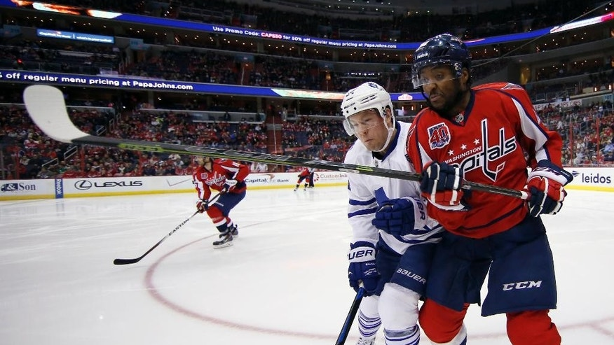 Toronto Maple Leafs center Peter Holland (24) checks Washington Capitals right wing Joel Ward (42) in the second period of an NHL hockey game, Sunday, March 1, 2015, in Washington. (AP Photo/Alex Brandon)