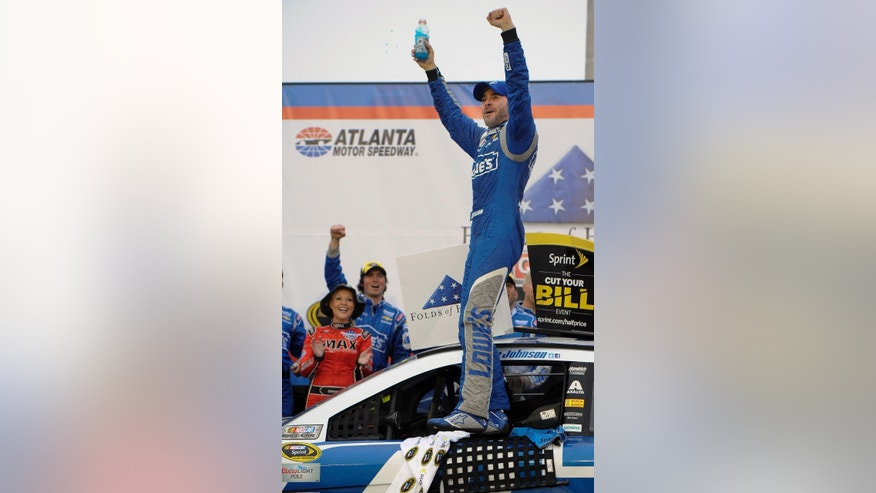 Jimmie Johnson reacts after winning the NASCAR Sprint Cup auto race at Atlanta Motor Speedway in Hampton, Ga., Sunday, March 1, 2015. (AP Photo/John Amis)
