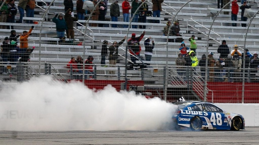 Jimmie Johnson (48) does a celebratory burnout after winning the NASCAR Sprint Cup series auto race at Atlanta Motor Speedway, Sunday, March 1, 2015, in Hampton, Ga. (AP Photo/John Bazemore)