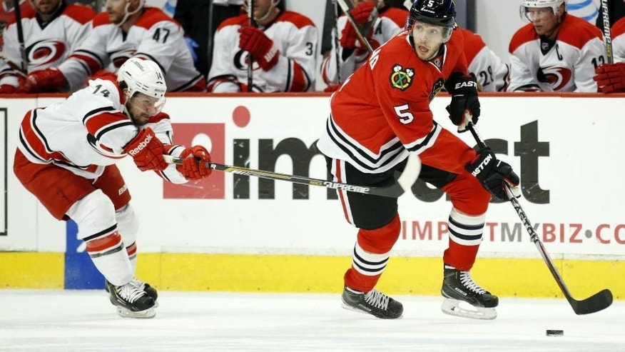 Chicago Blackhawks defenseman David Rundblad (5) skates with the puck past Carolina Hurricanes left wing Nathan Gerbe (14) during the first period of an NHL hockey game Monday, March 2, 2015, in Chicago. (AP Photo/Andrew A. Nelles)