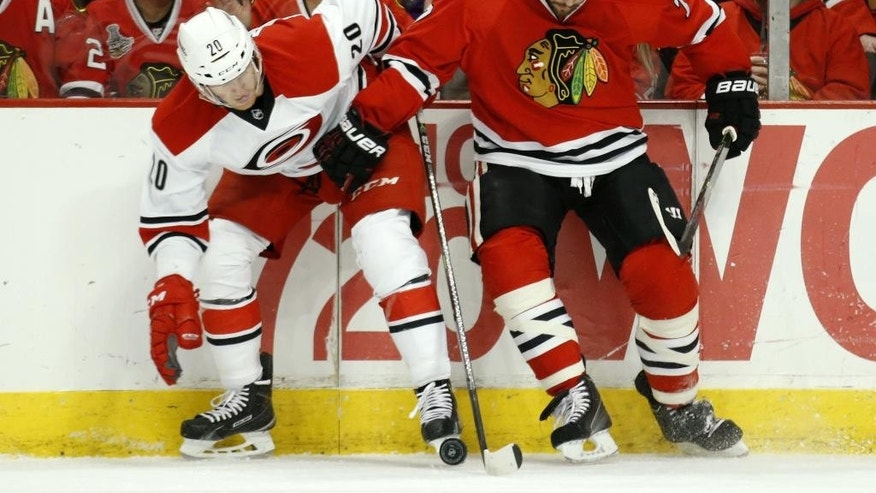 Carolina Hurricanes center Riley Nash (20) battles for the puck with Chicago Blackhawks defenseman Brent Seabrook (7) during the first period of an NHL hockey game Monday, March 2, 2015, in Chicago. (AP Photo/Andrew A. Nelles)