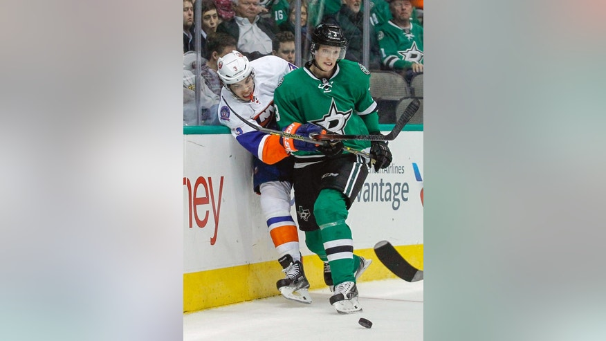 New York Islanders defenseman Travis Hamonic, left, is shoved against the boards by Dallas Stars defenseman John Klingberg in the second period of an NHL hockey game Tuesday, March 3, 2015, in Dallas.  (AP Photo/Tim Sharp)