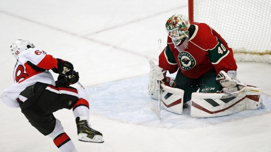 Minnesota Wild goalie Devan Dubnyk  deflects a shot by Ottawa Senators' Mike Hoffman, left, in the shootout as the Wild won 3-2 in an NHL hockey game, Tuesday, March 3, 2015, in St. Paul, Minn.v (AP Photo/Jim Mone)