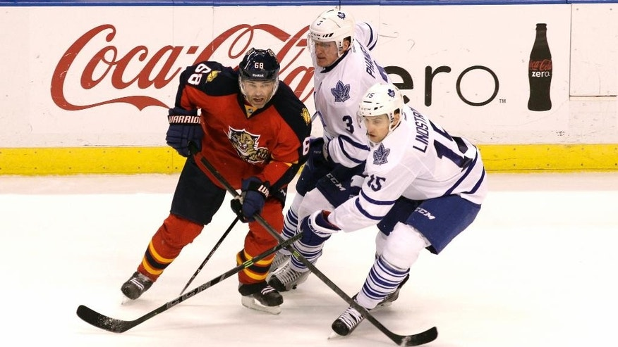 Florida Panthers' Jaromir Jagr (68), of the Czech Republic, moves the puck as Toronto Maple Leafs' Dion Phaneuf (3) and Joakim Lindstrom, of Sweden, during the second period of an NHL hockey game, Tuesday, March 3, 2015, in Sunrise, Fla. (AP Photo/Luis M. Alvarez)