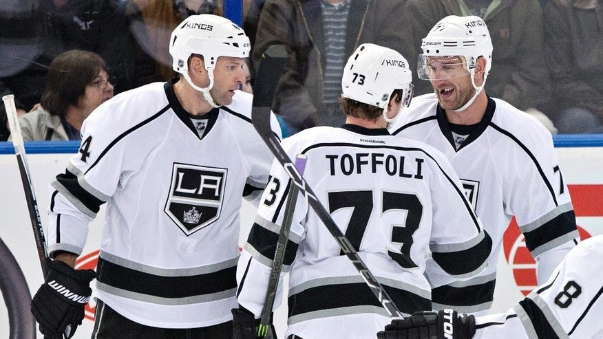 Los Angeles Kings' Robyn Regehr (44), Tyler Toffoli (73) and Jeff Carter (77) celebrate a goal against the Edmonton Oilers during the second period of an NHL hockey game in Edmonton, Alberta, Tuesday, March 3, 2015. (AP Photo/The Canadian Press, Jason Franson)