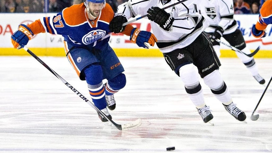 Los Angeles Kings' Anze Kopitar (11) and Edmonton Oilers' Benoit Pouliot (67) chase the loose puck during the first period of an NHL hockey game in Edmonton, Alberta, Tuesday, March 3, 2015. (AP Photo/The Canadian Press, Jason Franson)