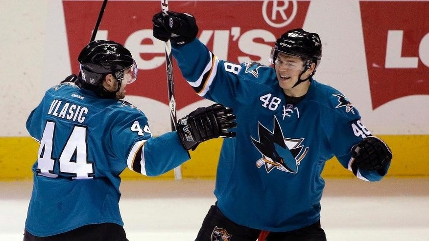 San Jose Sharks' Marc-Edouard Vlasic (44) celebrates with teammate Tomas Hertl (48) after Vlasic assisted on a goal by Ben Smith during the first period of an NHL hockey game Monday, March 2, 2015, in San Jose, Calif. (AP Photo/Marcio Jose Sanchez)