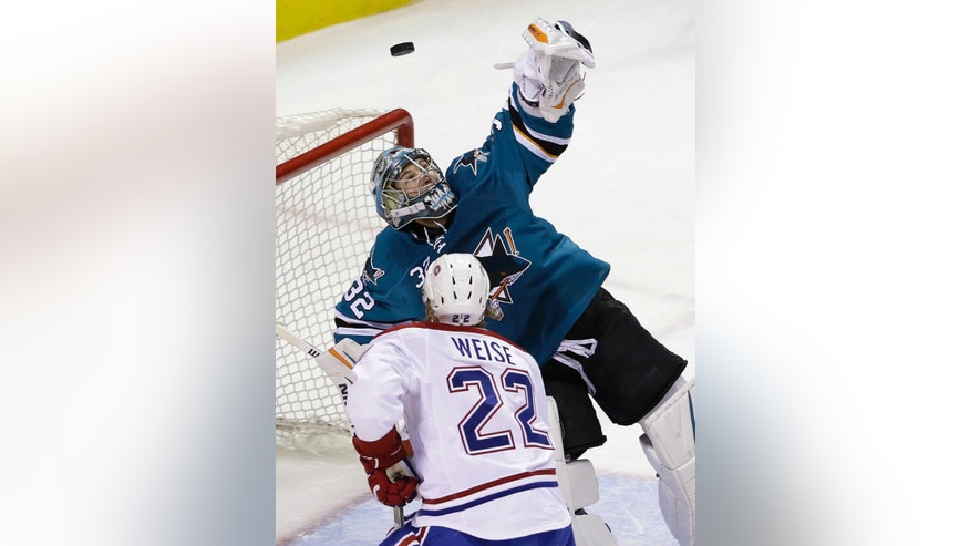 San Jose Sharks goalie Alex Stalock, top, deflects a shot next to Montreal Canadiens' Dale Weise (22) during the first period of an NHL hockey game Monday, March 2, 2015, in San Jose, Calif. (AP Photo/Marcio Jose Sanchez)