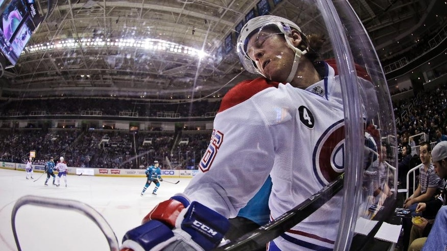 Montreal Canadiens' Jeff Petry is pressed against the boards by a San Jose Sharks player during the second period of an NHL hockey game Monday, March 2, 2015, in San Jose, Calif. (AP Photo/Marcio Jose Sanchez)