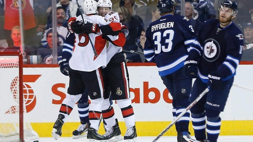 Ottawa Senators' Bobby Ryan (6) and Alex Chiasson (90) celebrate Ryan's goal against the Winnipeg Jets as Jets' Dustin Byfuglien (33) and Bryan Little (18) look on during second-period NHL hockey game action in Winnipeg, Manitoba, Wednesday, March 4, 2015. (AP Photo/The Canadian Press, John Woods)