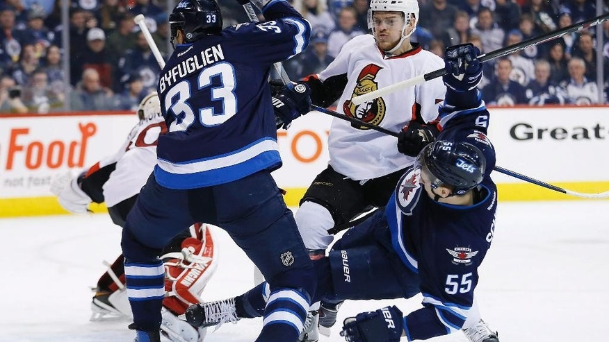 Ottawa Senators' Mark Borowiecki (74) clears Winnipeg Jets' Dustin Byfuglien (33) and Mark Scheifele (55) from in front of Senators goaltender Andrew Hammond's (30) net during second-period NHL hockey game action in Winnipeg, Manitoba, Wednesday, March 4, 2015. (AP Photo/The Canadian Press, John Woods)