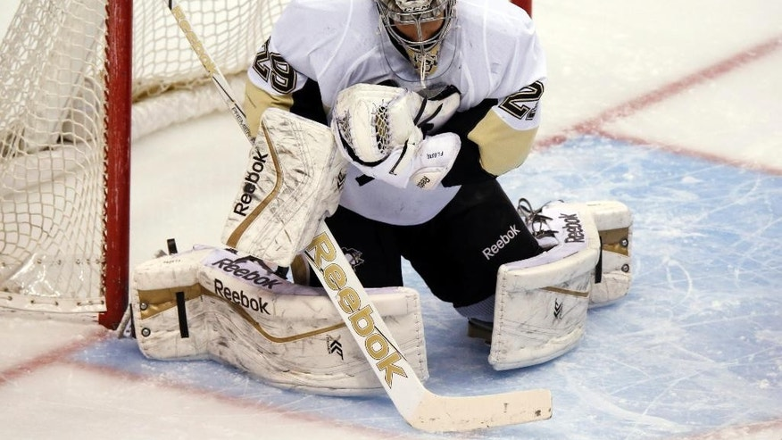 Pittsburgh Penguins goalie Marc-Andre Fleury makes a save of a shot off the stick of a Colorado Avalanche player in the first period of an NHL hockey game Wednesday, March 4, 2015, in Denver. (AP Photo/David Zalubowski)