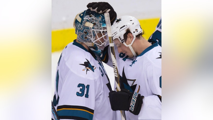 San Jose Sharks goalie Antti Niemi, left, of Finland, and teammate Justin Braun celebrate the team's 6-2 win over the Vancouver Canucks in an NHL hockey game Tuesday, March 3, 2015, in Vancouver, British Columbia. (AP Photo/The Canadian Press, Darryl Dyck)