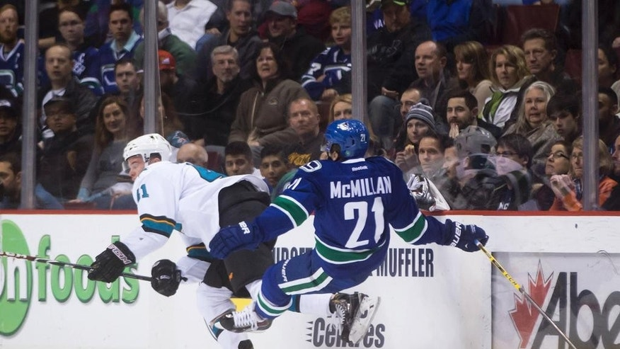 San Jose Sharks' Mirco Mueller, left, of Switzerland, and Vancouver Canucks' Brandon McMillan collide during the first period of an NHL hockey game Tuesday, March 3, 2015, in Vancouver, British Columbia. (AP Photo/The Canadian Press, Darryl Dyck)
