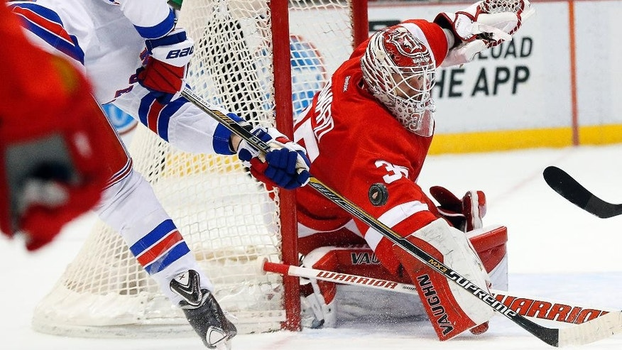 Detroit Red Wings goalie Jimmy Howard (35) stops a shot by New York Rangers right wing Jesper Fast during the first period of an NHL hockey game in Detroit on Wednesday, March 4, 2015. (AP Photo/Paul Sancya)