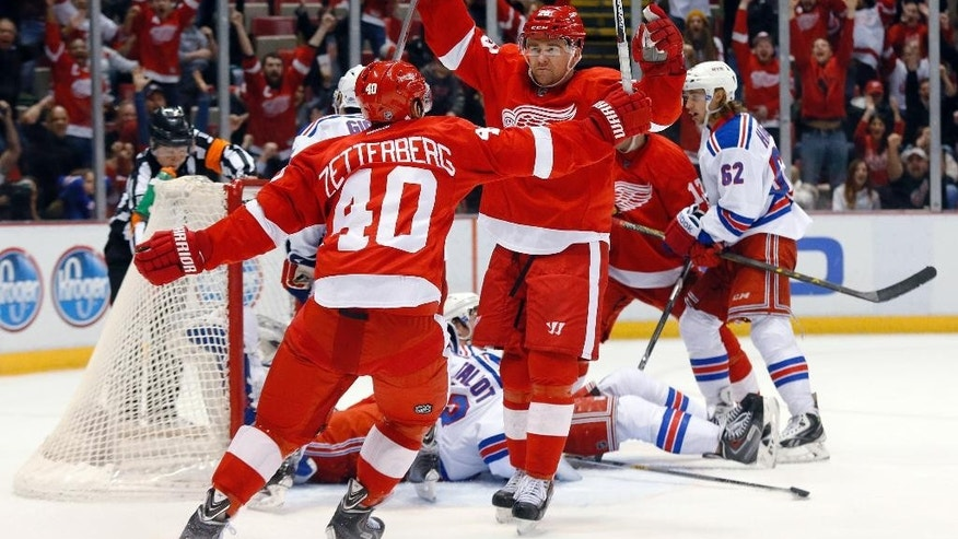 Detroit Red Wings' Marek Zidlicky, facing camera, celebrates his goal in overtime against the New York Rangers with Henrik Zetterberg (40) during an NHL hockey game in Detroit on Wednesday, March 4, 2015. Detroit won 2-1. (AP Photo/Paul Sancya)