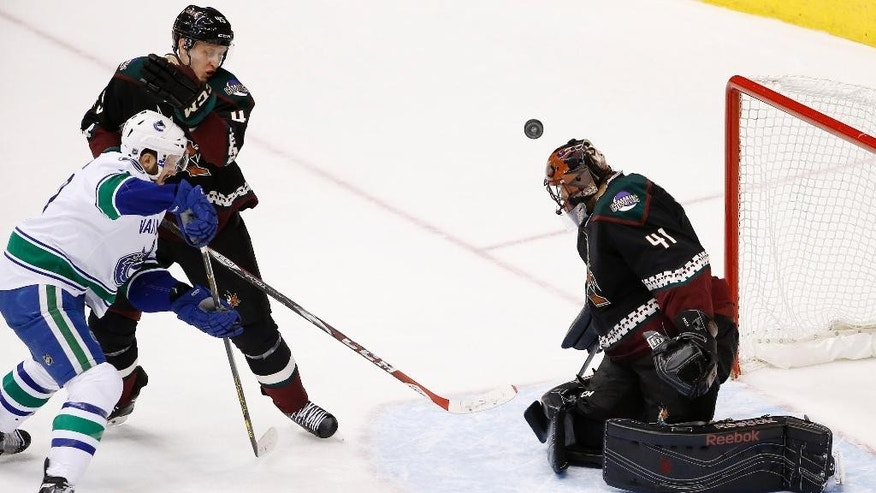 Arizona Coyotes' Mike Smith (41) makes a save on a shot by Vancouver Canucks' Nick Bonino, left, as Coyotes' Andrew Campbell, second from right, defends during the second period of an NHL hockey game Thursday, March 5, 2015, in Glendale, Ariz. (AP Photo/Ross D. Franklin)