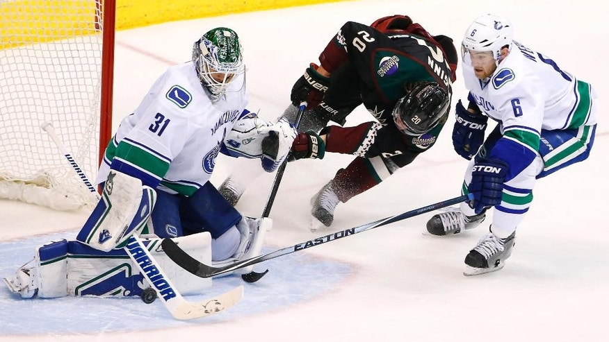 Vancouver Canucks' Eddie Lack (31) makes a save on a shot by Arizona Coyotes' Tye McGinn (20) as Canucks' Yannick Weber (6), of Switzerland, defends during the second period of an NHL hockey game Thursday, March 5, 2015, in Glendale, Ariz. (AP Photo/Ross D. Franklin)