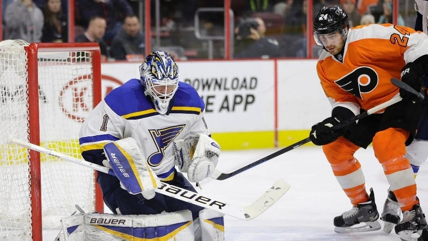 St. Louis Blues' Brian Elliott (1) blocks a shot as Philadelphia Flyers' Matt Read (24) looks for the rebound during the second period of an NHL hockey game, Thursday, March 5, 2015, in Philadelphia. (AP Photo/Matt Slocum)