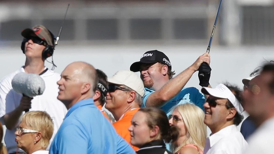 J.B. Homes, center rear, watches his shot after hitting from out of bounds of the first fairway during the first round of the Cadillac Championship golf tournament, Thursday, March 5, 2015, in Doral, Fla. (AP Photo/Wilfredo Lee)