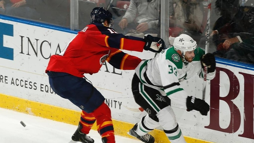 Florida Panthers forward Jonathan Huberdeau (11) checks Dallas Stars defenseman Alex Goligoski (33) off the puck behind the net during the second period of an NHL hockey game, Thursday, March 5, 2015, in Sunrise, Fla. (AP Photo/Joel Auerbach)