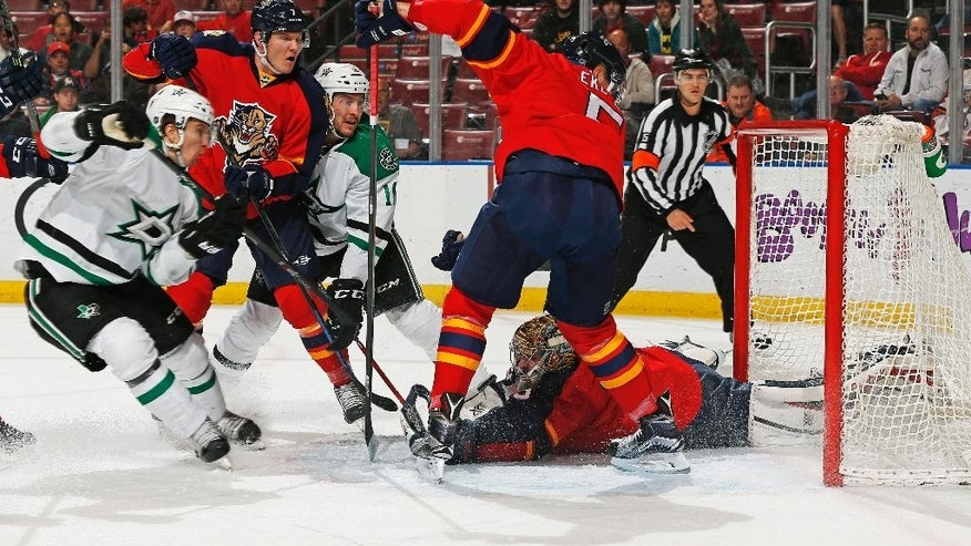 Florida Panthers goaltender Dan Ellis (39) stops a shot by Dallas Stars forward Ryan Garbutt, third from left, during the first period of an NHL hockey game, Thursday, March 5, 2015, in Sunrise, Fla. (AP Photo/Joel Auerbach)