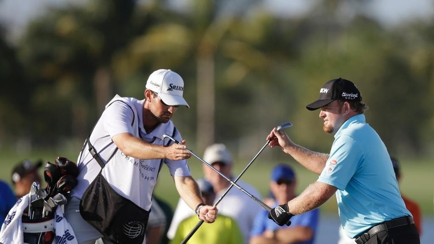 Caddie Brandon Parsons, left, hands J.B. Holmes a club as Holmes switches clubs before hitting out of a bunker on the ninth hole during the first round of the Cadillac Championship golf tournament, Thursday, March 5, 2015, in Doral, Fla. (AP Photo/Wilfredo Lee)