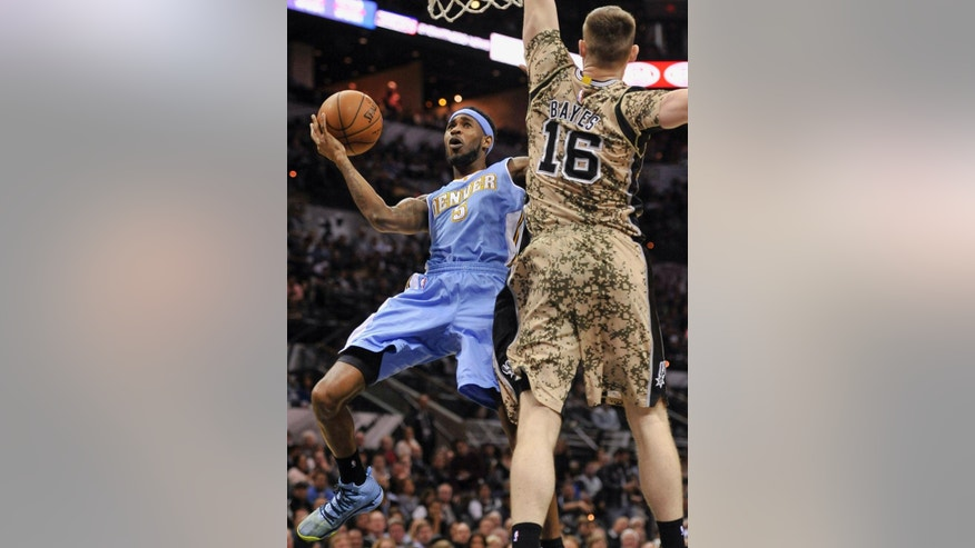Denver Nuggets guard Will Barton, left, shoots against San Antonio Spurs forward Aron Baynes, of Australia, during the first half of an NBA basketball game, Friday, March 6, 2015, in San Antonio. (AP Photo/Darren Abate)