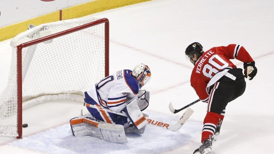 Chicago Blackhawks center Antoine Vermette (80) scores between the legs of Edmonton Oilers goalie Ben Scrivens, giving the Blackhawks a 2-1 win during a shootout period of an NHL hockey game Friday, March 6, 2015, in Chicago. (AP Photo/Charles Rex Arbogast)