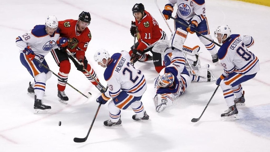 Edmonton Oilers center Matt Hendricks (23) clears the puck away from his goalie Ben Scrivens and other teammates during the second period of an NHL hockey game against the Chicago Blackhawks, Friday, March 6, 2015, in Chicago. (AP Photo/Charles Rex Arbogast)