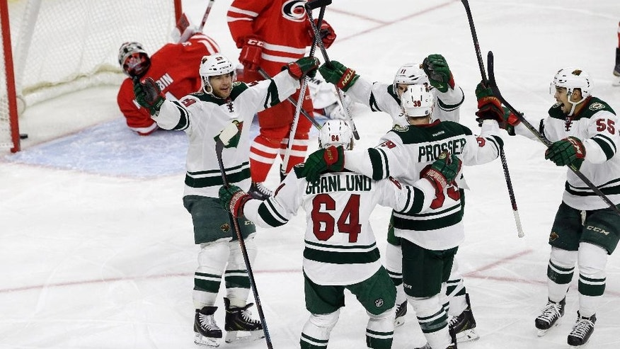 Minnesota Wild's Mikael Granlund (64), of Finland, celebrates his goal against the Carolina Hurricanes with Jason Pominville (29), Nate Prosser, Zach Parise (11) and Matt Dumba (55) during the third period of an NHL hockey game in Raleigh, N.C., Friday, March 6, 2015. Minnesota won 3-1. (AP Photo/Gerry Broome)